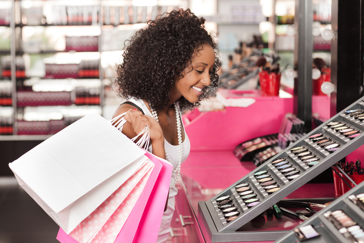 Shopping woman looking for eye shadow in the beauty store.
