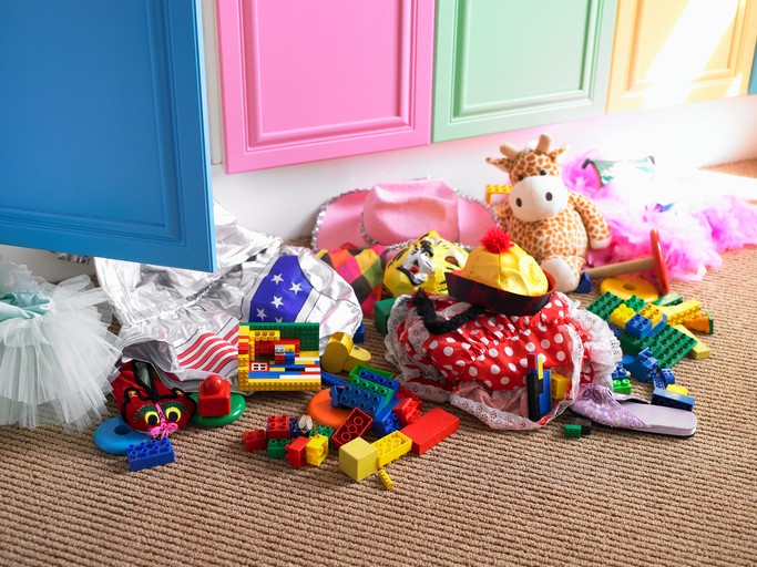 Children's toys and items of clothing strewn on floor near open cupboard door in bedroom