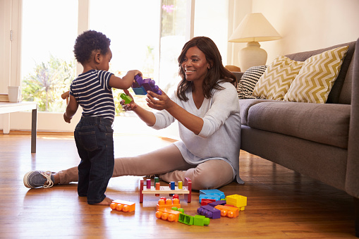 Mother And Son Playing With Toys On Floor At Home