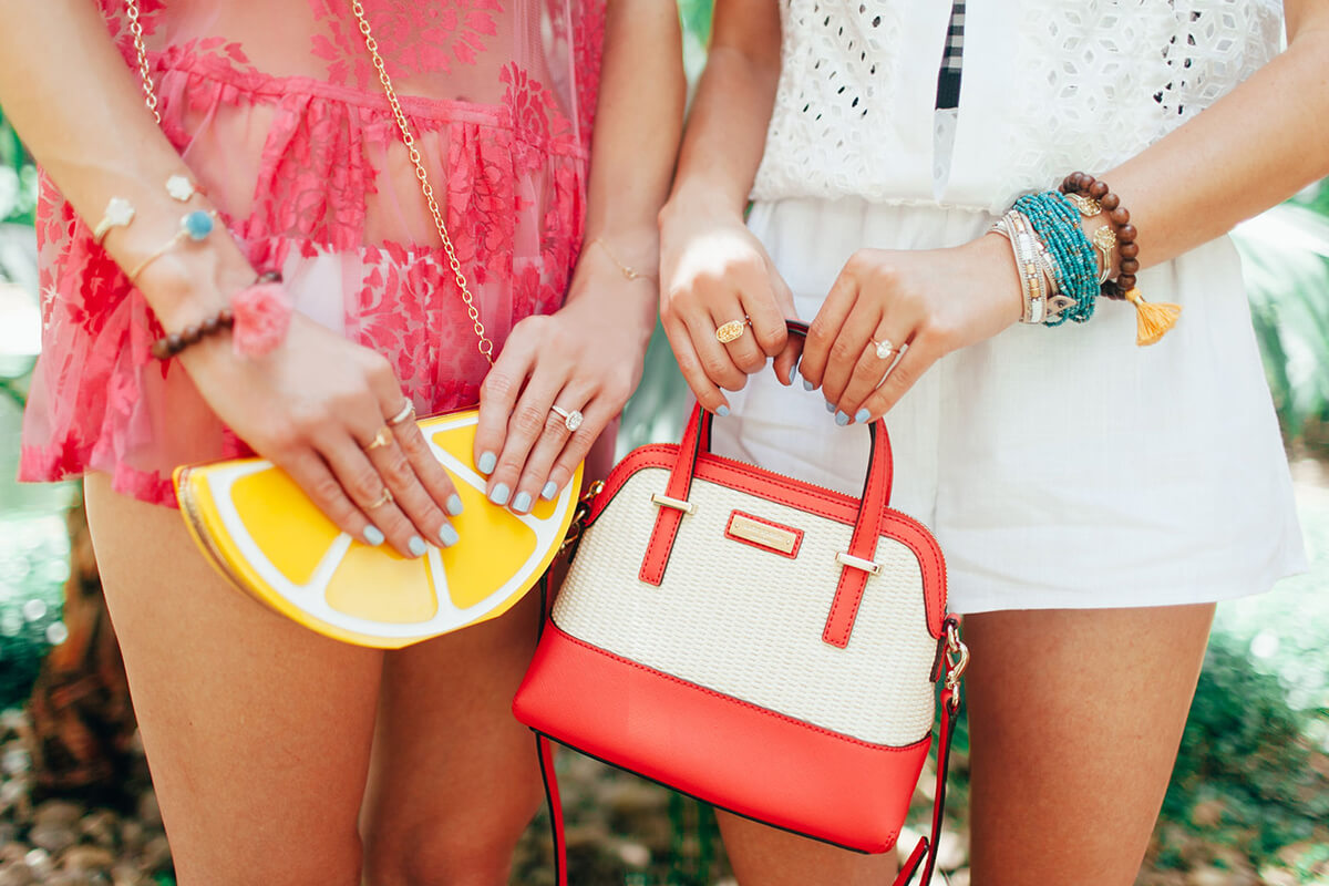 Two girls holding purses and wearing jewelry
