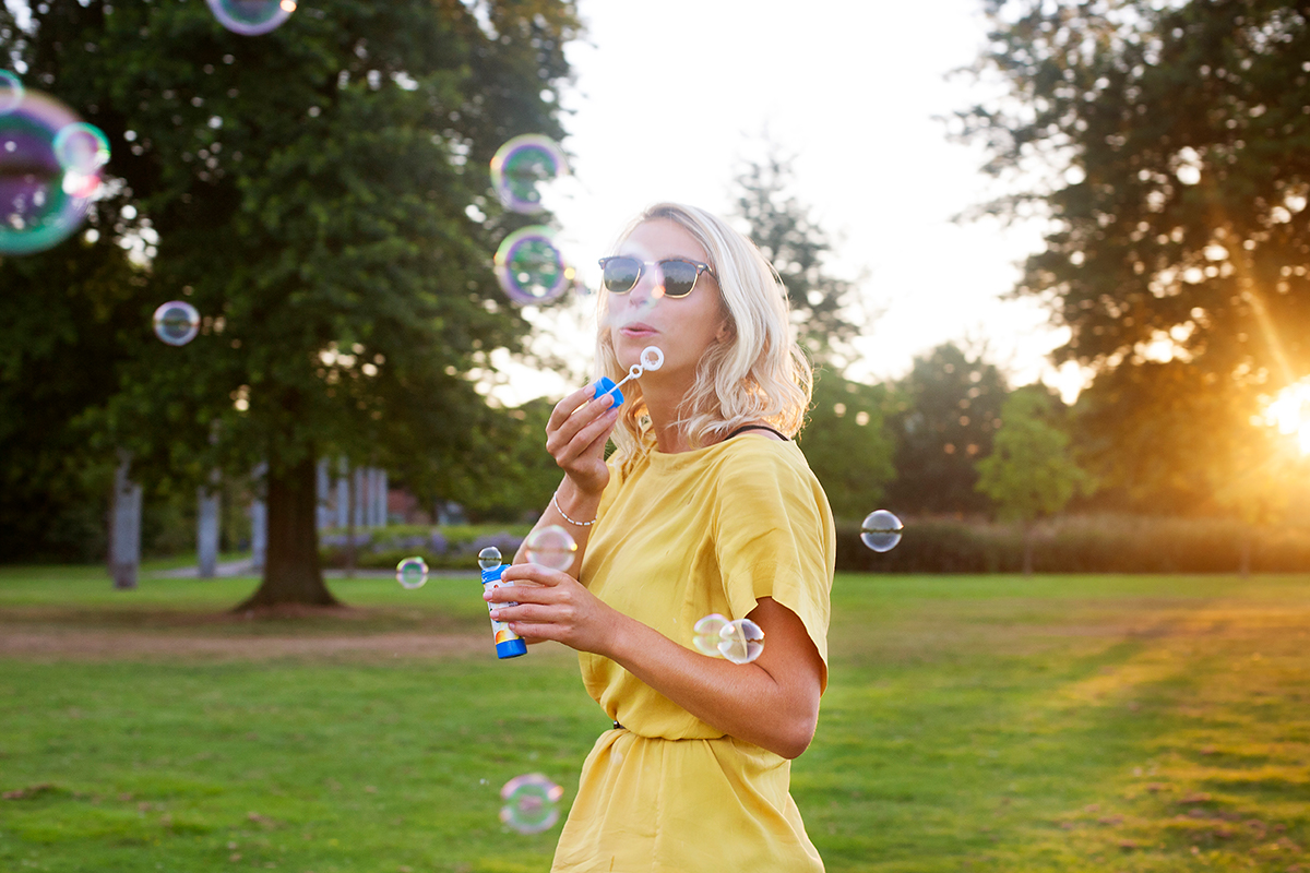 Girl in a yellow dress blowing bubbles
