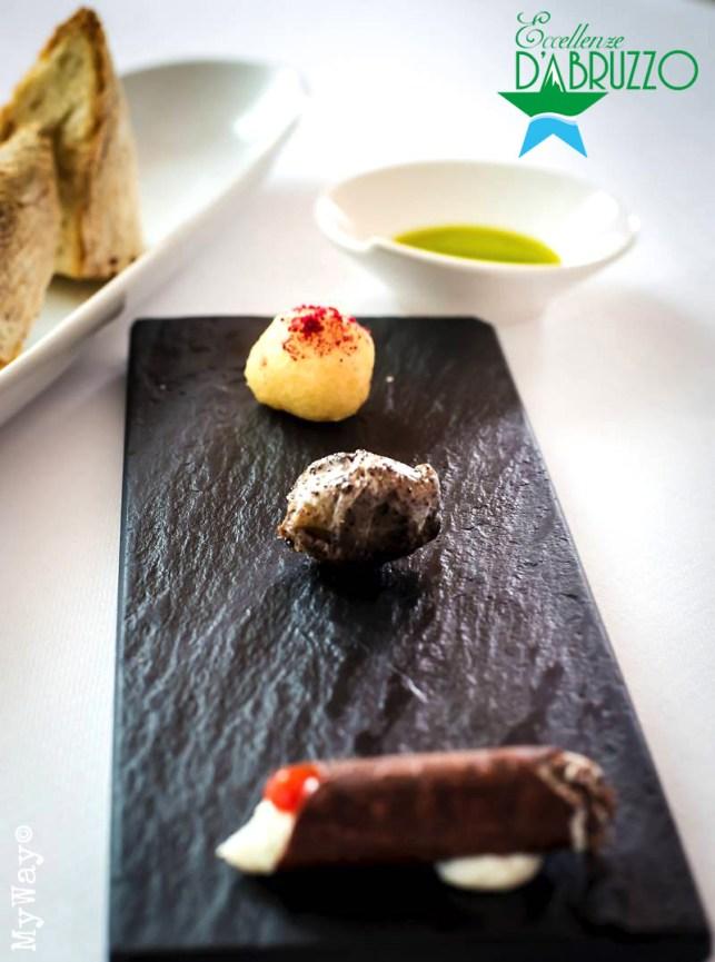 Zeppola di baccalà con polvere di lampone, Oliva caramellata farcita di acciughe, Cannolo al cioccolato con mousse di ricotta