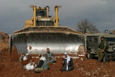 Palestinian farmers sit in front of a di