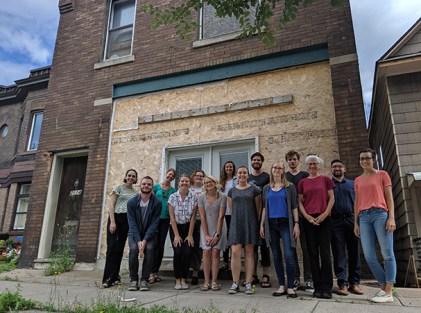 AmeriCorps VISTA volunteers stand in front of Legacy House Building before reconstruction.