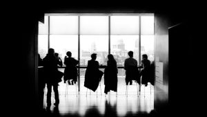 6 attendees silhouetted seated by a window at a workshop