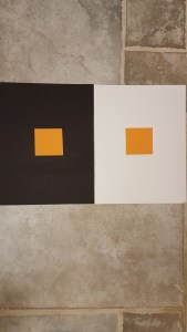 Orange squares of same size on black and white sheets.