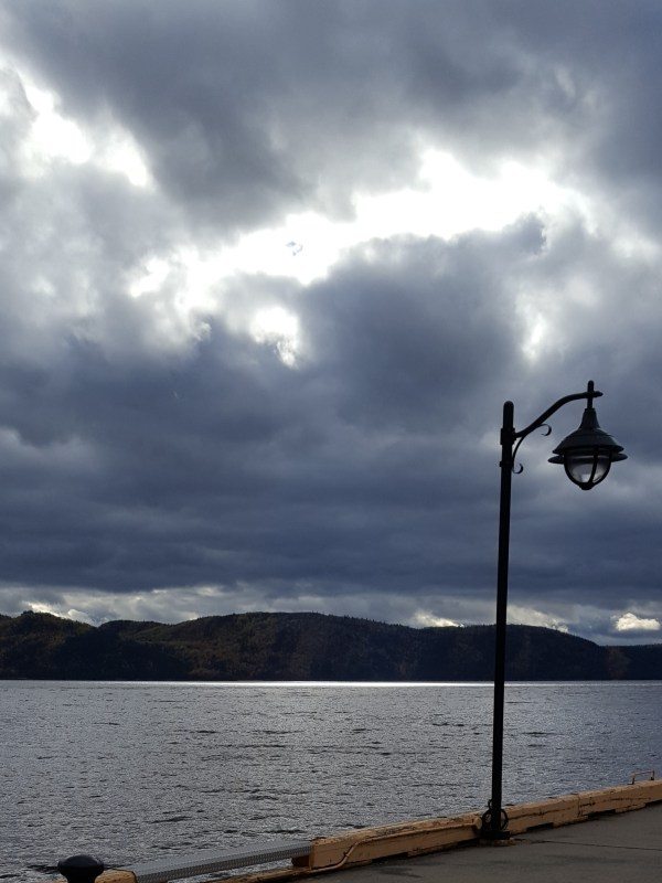 Lamp post on pier with fjord in background