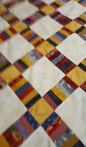 Quilt using mustard yellow, garnet and gray-blue colors as a base
