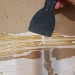 Hand scraping tile glue from wall