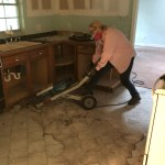 Econogal using a jackhammer to break tile floor
