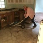 Econogal using a jackhammer to break tile floor