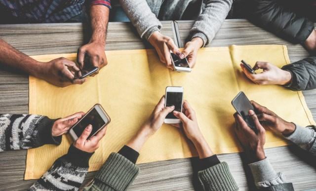 ανδρες με κινητά στα χέρια, σε τραπέζι