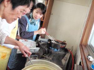 参加者がフライを揚げている横で、桑原さんが汁物を温めています。鍋の中が気になる参加者。