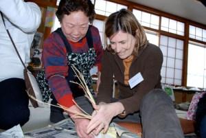 野菜をワラで編み込み、つるして干す保存方法を体験。