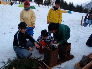 雪の上でのたき火は、一斗缶を使って起こします。後ろのテント群がお泊まりの場所となりました。