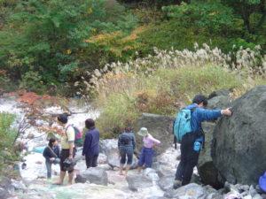 以前硫黄を採掘していた現場で温泉が川に流れ出ていた。みんな思い思いの場所で「足湯」を楽しむ