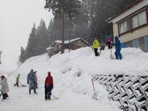 屋根からの落ちて積み上がった雪をさらに下に押し出していく。