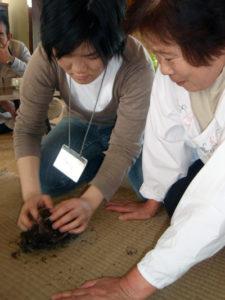 ゼンマイの揉み方を教える集落のおかあさんと、山菜採り初体験の参加者。