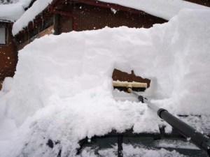車の屋根の雪をどかしています。下の雪を押しても、上の雪は動きませんでした。