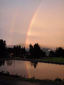 溜め池の水鏡に移る虹。