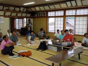 岩手宮城内陸地震の被害と復興状況を説明するくりこま高原自然学校の佐々木豊志さん(中央右)