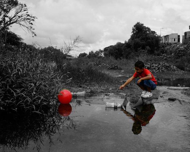 Chico en río contaminado