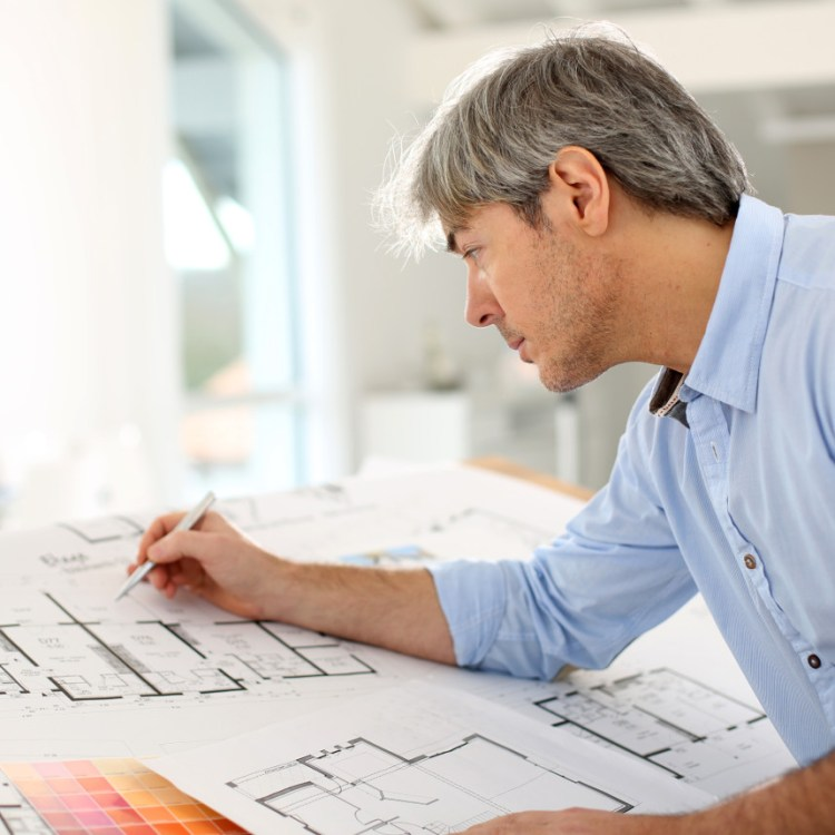 An architect drawing up plans for a villa in Spain