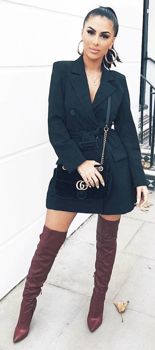 black double-breasted dress and pair of brown slouchy thigh-high boots