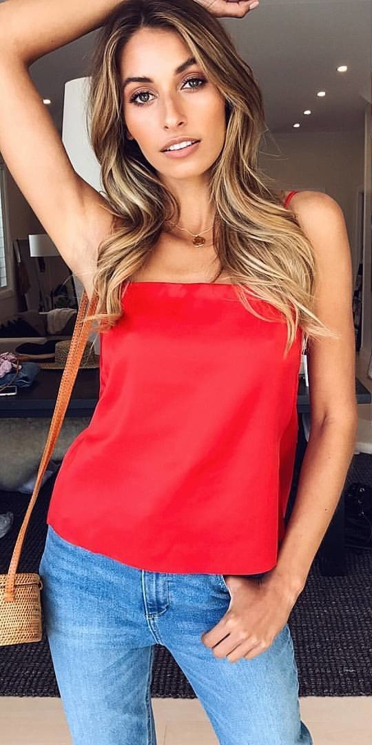 women's red spaghetti-strap top and blue denim jeans