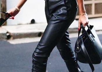 Woman walking wearing blue crew-neck shirt and black faux leather skinny jeans outfit.