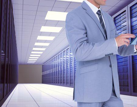 Digital composition of businessman using digital tablet against server room background