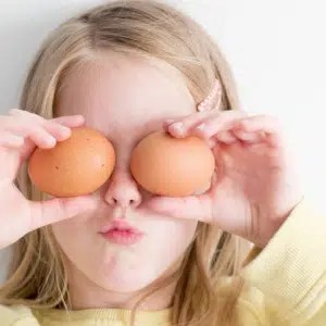 girl holding eggs up to cover her eyes