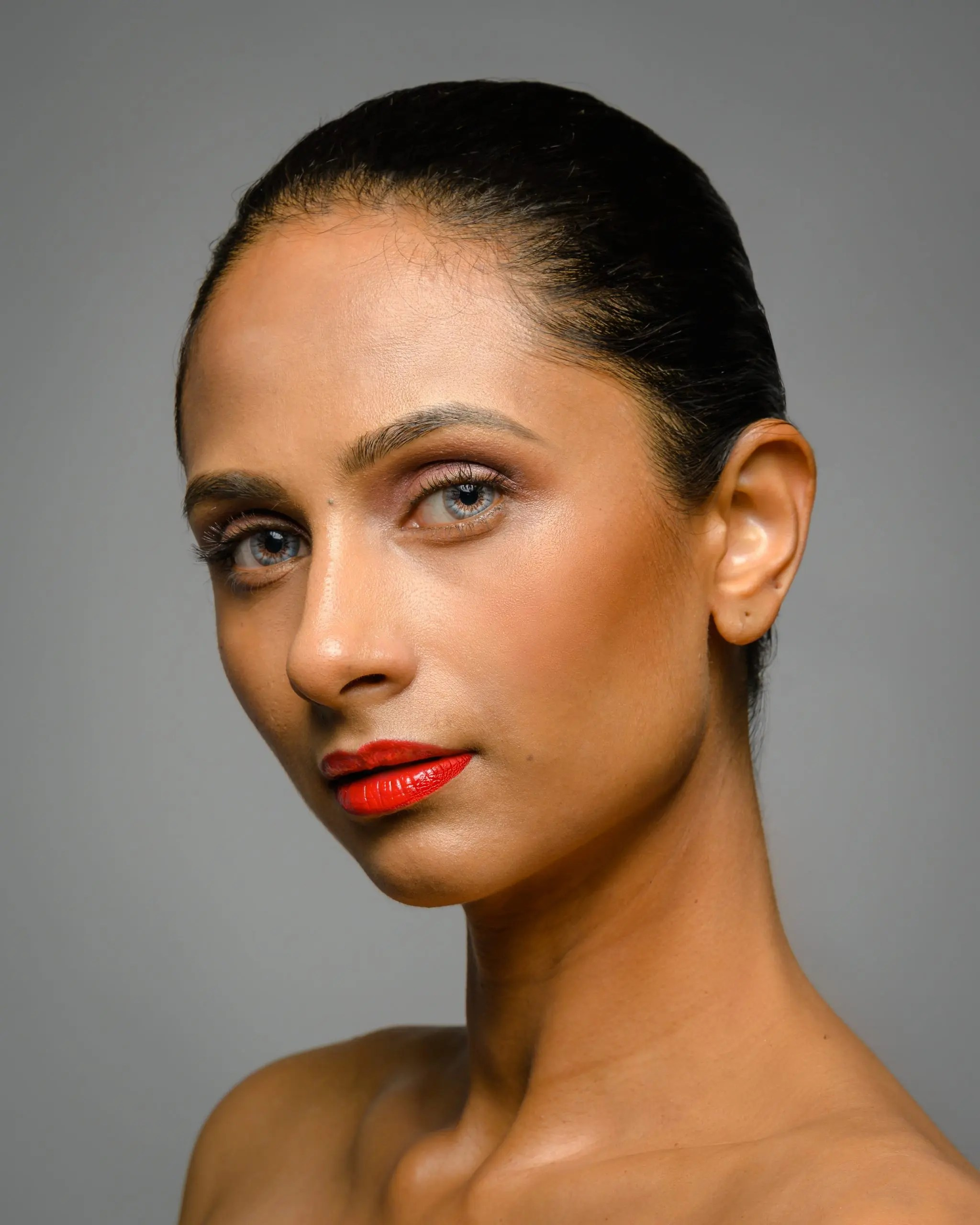 Studio photography with a female model posing for beauty and makeup headshots with hair slicked back in a tight bun.