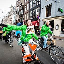 Activists ride bikes through the streets of Amsterdam on Global Divestment Day. Credit: Nichon Glerumwww.nichon.nl