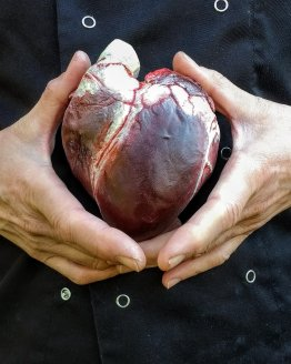 a realistic Human Heart made from dark chocolate held in a woman's hand