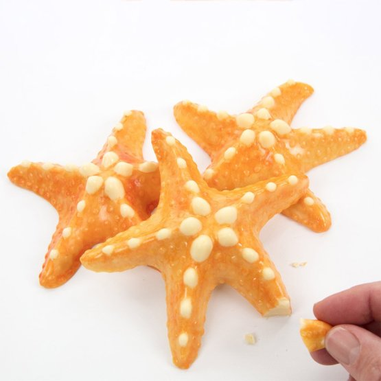 A hand snaps a piece off a white chocolate starfish against a white background