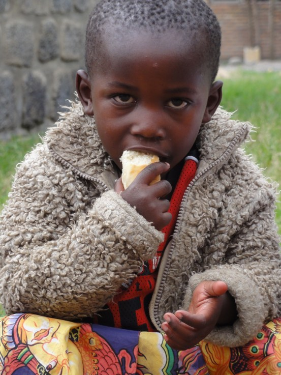 A young Rwandan girl in the northern city of Musanze eats a morning meal of bread and porridge during morning break