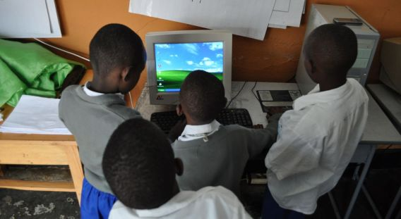 A group of young Rwandan students gather around a computer at a school in Kigali to discover more about what they have been taught in the classroom.