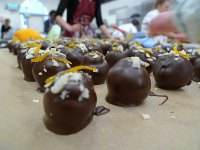 Orange and cardamon ganache covered in dark chocolate and decorated with almonds and candied orange peel. Look at us work.