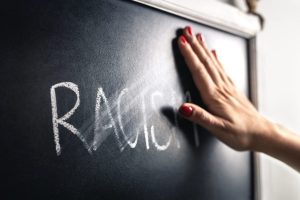 Hand rubbing out the word racism on a chalkboard.