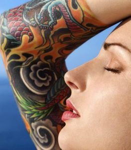 woman with tattoo sunbathes