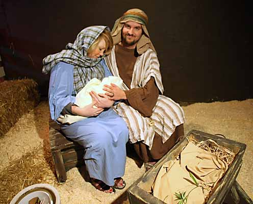 Mary and Joseph, Jennifer and Andrew Lee, hold the baby Jesus, in the stable in the recreated town.