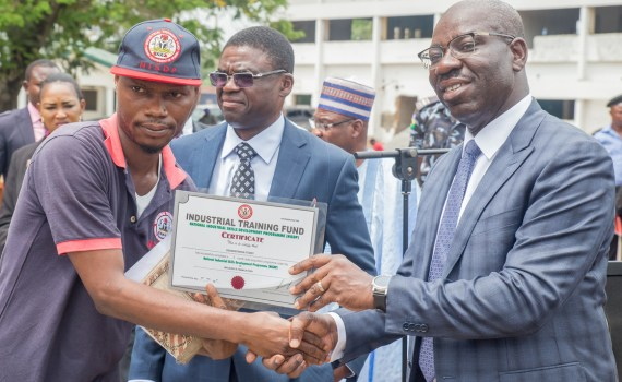 Governor Godwin Obaseki of Edo State (right), presenting a certificate to one of the participants in the National Industrial Skills Development Programme (NISDP), while the Deputy Governor, Rt. Hon. Philip Shaibu, looks on, during the closing ceremony of the NISDP Phase II organised by the Industrial Training Fund (ITF) in collaboration with the state government, in Government House, Benin City, on Wednesday, October 18, 2017.