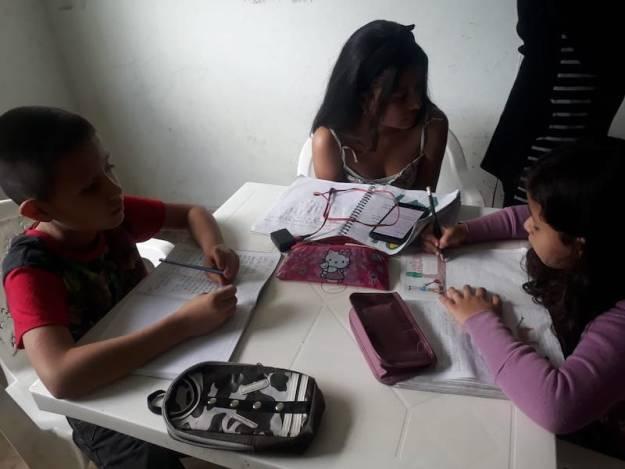 Tres niños estudiando en un celular
