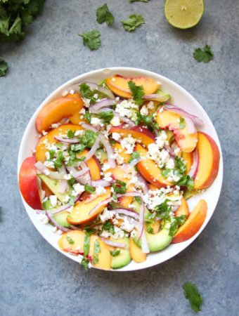 Peach, avocado and feta salad in a white bowl, on a gray background.