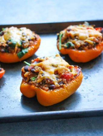 3 quinoa and black bean stuffed peppers on a black sheet pan, sitting on a gray surface.