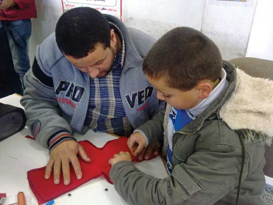 Child and parent during a doll-making activity at a parents' club