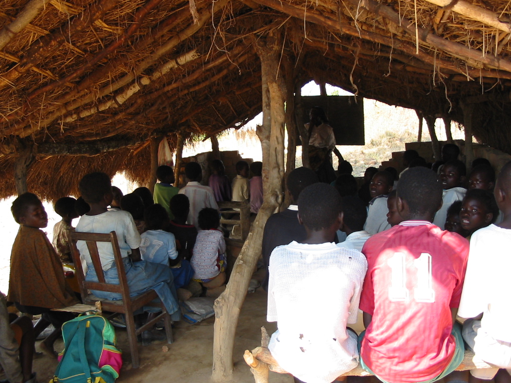 Children sit with backs to us in a classroom with simple pitched thatched roof with no walls