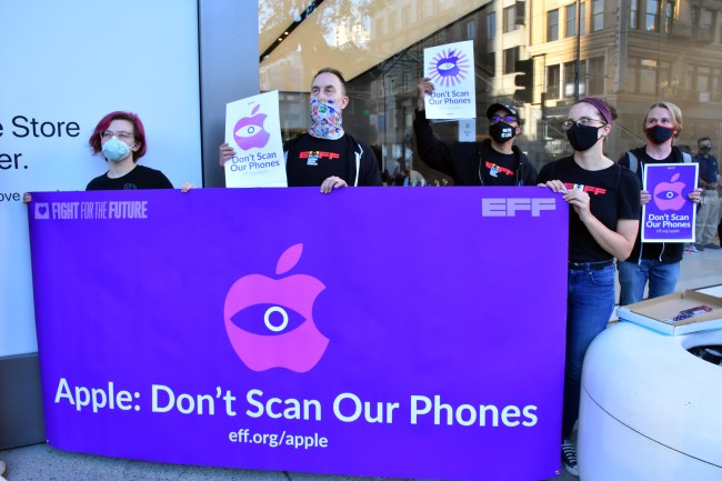 several people hold a banner that reads apple don't scan our phones in front of the apple store in san francisco