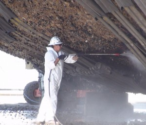dockyard worker cleaning barnacles from a boat hull